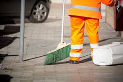 Horizontal View of a Dustman Cleaning the Street With a Mop Wear Stock Image