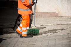 Horizontal View of a Dustman Cleaning the Street With a Mop Wear. Ing an Orange Uniform in a Sunny Day Stock Photo