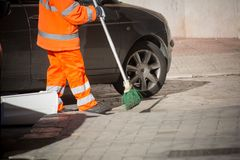 Horizontal View of a Dustman Cleaning the Street With a Mop Wear Royalty Free Stock Photography