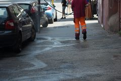 Horizontal View of a Dustman Cleaning the Street With a Water Pr. Essure Machine. Rome, Italy Royalty Free Stock Photography