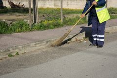 Horizontal View of a Dustman Working in the Street Using a Woode. N Mop and Dressing a Yellow Jacket on Blur Background Royalty Free Stock Photos
