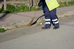 Horizontal View of a Dustman Working in the Street Using a Woode. N Mop and Dressing a Yellow Jacket on Blur Background Royalty Free Stock Image