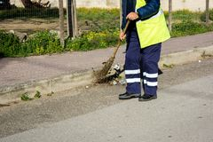 Horizontal View of a Dustman Working in the Street Using a Woode. N Mop and Dressing a Yellow Jacket on Blur Background Royalty Free Stock Photo