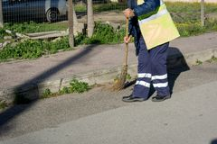 Horizontal View of a Dustman Working in the Street Using a Woode. N Mop and Dressing a Yellow Jacket on Blur Background Royalty Free Stock Images