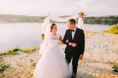 The horizontal view of the happy newlyweds walking arm in arm near the river. Stock Photos