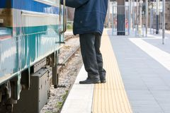 Horizontal View of a Man Standing near a Train at the Railway St. Ation on Blur Background. Taranto, South of Italy Royalty Free Stock Photography