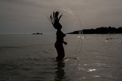 Horizontal View of a Silhouette of a Young Girl Splashing the Wa stock image