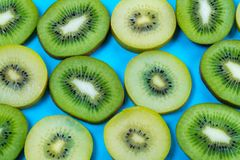 Selection of slices of yellow and green kiwi fruit on a bright high contrast turquoise background. Horizontal view of slices of golden yellow and green kiwi stock photo