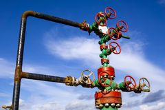 Horizontal view of a wellhead with valve armature. Oil and gas industry concept. Industrial site background. Toned. Horizontal view of a wellhead with valve royalty free stock photo