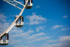 Horizontal View of a White Ferris Wheel on Partially Cloudy Sky. Background Royalty Free Stock Image