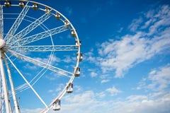 Horizontal View of a White Ferris Wheel on Partially Cloudy Sky. Background Stock Photos