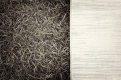 Horizontal vintage sepia picnic bamboo bedding on grass backgrou Royalty Free Stock Photos