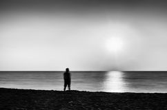 Horizontal vivid black and white lonely man meeting ocean sunset Royalty Free Stock Photos