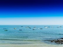 Horizontal vivid indian boats in ocean horizon background. Blank empty space sparse vibrant bright color rich blue clear sky gradient goa sea transportation royalty free stock photos