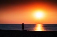Horizontal vivid man meeting ocean sunset Stock Image