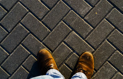 Horizontal vivid sunset boots on textured pavement Royalty Free Stock Photos