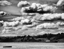 Horizontal vivid vibrant black and white Russian river with dramatic clouds royalty free stock images