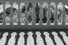 Horizontal white-painted castle balustrade in backlight. Horizontal white-painted castle balustrade with concrete casting rails in backlight and shadows on the royalty free stock photo