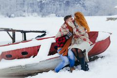 Horizontal winter portrait of the cheerful loving couple. The charming woman is softly stroking the cheek of the man. Horizontal winter portrait of the cheerful Stock Image