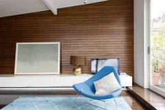Horizontal wood panelling in mid century living room. Horizontal wood panelling and blue occasional chair in mid century modern living room Royalty Free Stock Images