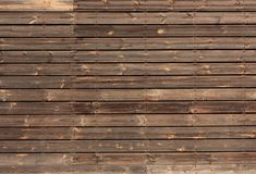 Horizontal wooden boards tinted in brown color. The wall of wooden boards tinted in brown and nailed in a horizontal direction. There are lots of knots on the royalty free stock image