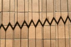 Horizontale achtergrond van ingekerfte schaduw van de rooster op de bruine vloertegels met kleine deuken, krassen en builen stock foto