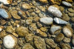 Horizontale achtergrond van rivier en rotsen met flikkering en bezinningen stock afbeelding
