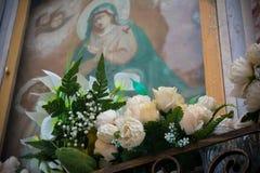 Horizontale Ansicht einer votive katholischen Ikone verziert mit Blumen lizenzfreie stockfotografie