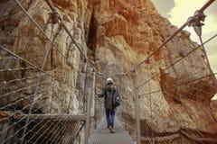 horizontale Ansicht eines jungen abenteuerlichen Mannes mit dem Sturzhelm, der eine Brücke kreuzt Stockfoto