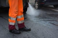 Horizontale Ansicht eines Müllabfuhrmannes Cleaning die Straße mit einer Wasser-PR stockfotografie