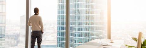 Horizontale Geschäftsmannstellung der hinteren Ansicht des Bildes, die durch panoramisches Fenster schaut lizenzfreies stockbild