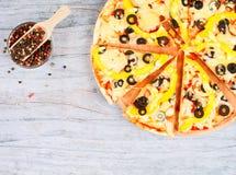 Horizontale Lebensmittelfahne mit cutted Pizza, Pfefferkörner auf hölzernem Hintergrund Leerer Platz für Text Stockfotografie