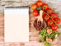 Horizontale Lebensmittelfahne mit Kirschtomaten, Arugula, Knoblauch, Pfefferkörnern und Notizbuch auf hölzernem Hintergrund Leere Lizenzfreie Stockfotografie
