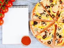 Horizontale Lebensmittelfahne mit Kirschtomaten, cutted Pizza, Gewürz und Notizbuch auf hölzernem Hintergrund Leerer Platz für Te Lizenzfreie Stockbilder