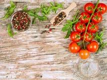 Horizontale Lebensmittelfahne mit Kirschtomaten, frischem Arugula und Pfefferkörnern auf hölzernem Hintergrund und copyspace Lizenzfreie Stockfotos