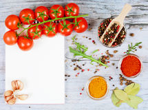 Horizontale Lebensmittelfahne mit Kirschtomaten, Knoblauch, Pfefferkörnern, Gewürz und Notizbuch auf hölzernem Hintergrund Leerer Lizenzfreie Stockfotos