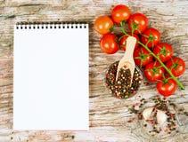 Horizontale Lebensmittelfahne mit Kirschtomaten, Knoblauch, Pfefferkörnern und Notizbuch auf hölzernem Hintergrund Leerer Platz f Lizenzfreies Stockfoto