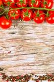 Horizontale Lebensmittelfahne mit reifen roten Kirschtomaten und Pfefferkörnern auf hölzernem Hintergrund Leerer Platz für Text Lizenzfreies Stockbild
