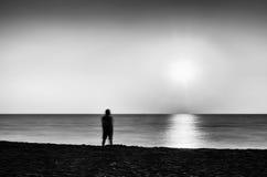 Horizontale levendige zwart-witte eenzame mens die oceaanzonsondergang ontmoeten Royalty-vrije Stock Foto's