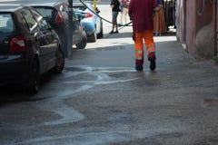 Horizontale Mening van Dustman Cleaning de Straat met een Water PR royalty-vrije stock fotografie