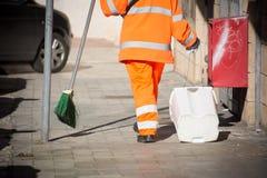Horizontale Mening van Dustman Cleaning de Straat met een Zwabberslijtage Stock Foto's