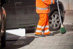 Horizontale Mening van Dustman Cleaning de Straat met een Zwabberslijtage Royalty-vrije Stock Afbeeldingen