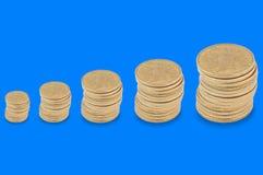 Horizontale rij van stapels vele gele muntstukken van klein tot groot op blauwe achtergrond stock fotografie