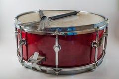 Horizontale rote hölzerne Schnarrtrommel und Jazzbürsten lokalisiert auf a lizenzfreies stockbild