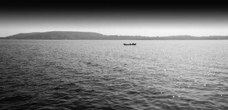 Horizontale zwart-witte boot in oceaanhorizonlandschap backg Stock Afbeeldingen