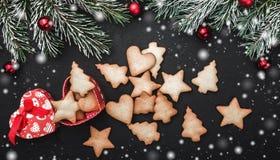Horizontale zwarte steenachtergrond met spartakken Sneeuweffect Een hart-vormige doos van koekjes van diverse vormen stock afbeeldingen