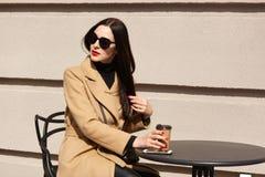 Horizontaler Schuss der jungen schönen brunette Frau in der stilvollen Sonnenbrille und beige im Mantel, die bei Tisch Café im im stockfotos