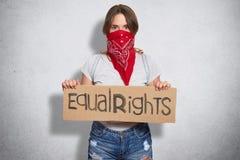 Horizontaler Schuss der schönen jungen Frau gehören feministischer Bewegung, trägt roten Bandana auf Gesicht, hält Platte mit Auf lizenzfreie stockfotografie