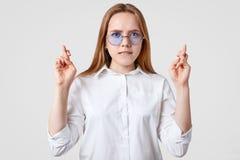 Horizontaler Schuss der wünschenswerten jungen Frau hält Finger gekreuzt, die Hoffnungen für gutes Glück, gekleidet im weißen Hem stockfotografie