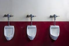Horizontaler Schuss von drei Toiletten auf einer roten und weißen Wand stockfotografie